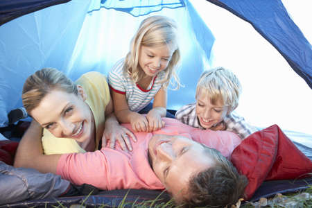 horsing around: Young family playing in tent