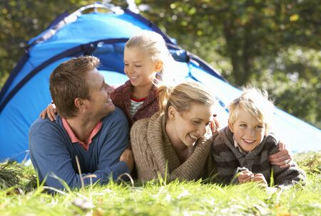 Young family poses outside of tent photo