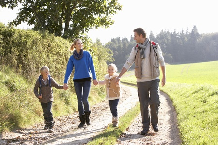 Young family walking in park photo