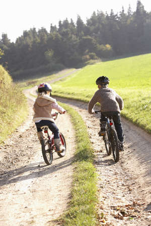 Two young children ride bicycles in park photo