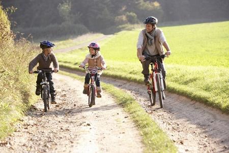 ni�os en bicicleta: Padre de joven con ni�os montar bicicleta en el Parque