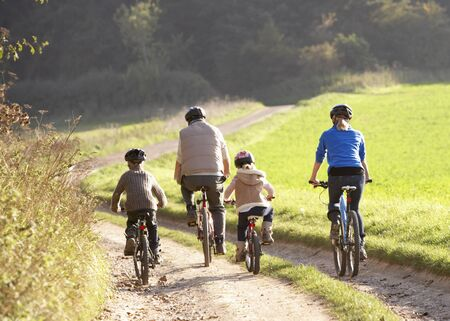 backview: Young parents with children ride bikes in park Stock Photo