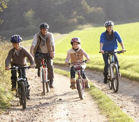 Young parents with children ride bikes in park photo