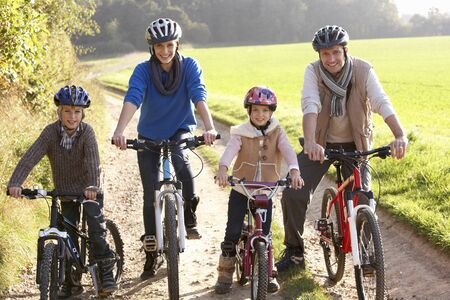 active family: Young family pose with  bikes in park Stock Photo