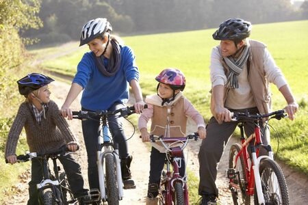 biking: Young family pose with  bikes in park Stock Photo