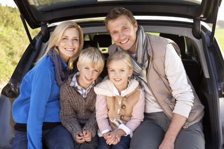 Young family pose together at rear of car photo