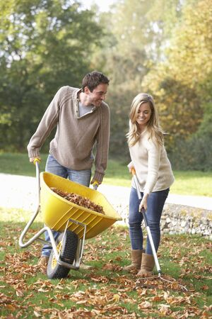 30 years old: Young couple raking autumn leaves in garden