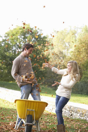 Young couple having fun with autumn leaves in garden photo