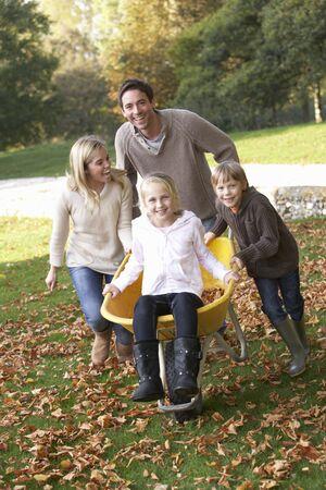 carretilla: Familia se divierte con las hojas de oto�o en el jard�n Foto de archivo