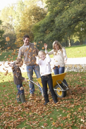 Family throwing autumn leaves into the air in garden photo