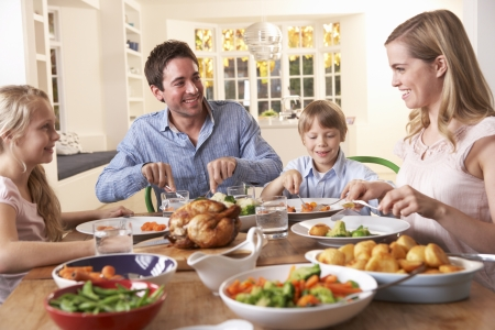 dinner table: Happy family having roast chicken dinner at table Stock Photo