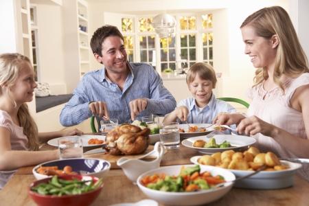 Happy family having roast chicken dinner at table photo