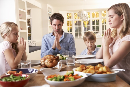praying together: Family Saying Prayer Before Eating Roast Dinner Stock Photo