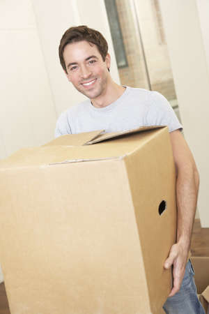 Young man on moving day holding and carrying cardboard box photo