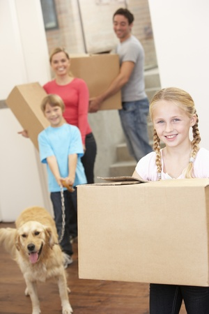Family with dog on moving day carrying cardboard boxes photo