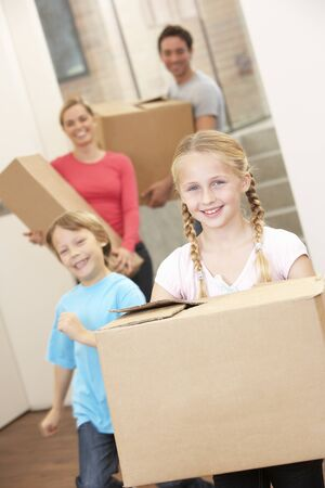 out of the box: Family happy on moving day carrying cardboard boxes