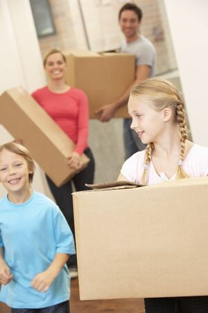 relocating: Family happy on moving day carrying cardboard boxes