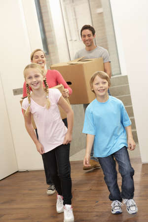 10 years girls: Family happy on moving day carrying cardboard boxes