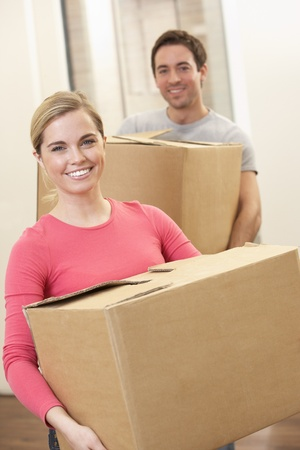 Young couple on moving day carrying cardboard boxes Stock Photo - 9875585