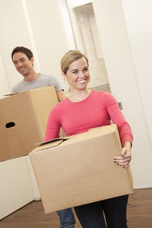 Young couple on moving day carrying cardboard boxes photo