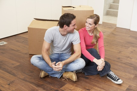 Young couple on moving day sitting with cardboard boxes Stock Photo - 9876128