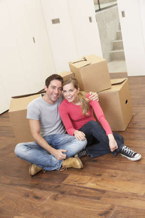 Young couple on moving day sitting with cardboard boxes Stock Photo - 9876055