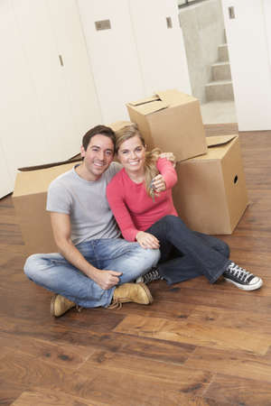 Young couple on moving day sitting with cardboard boxes Stock Photo - 9876040