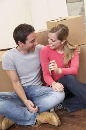 Young couple on moving day sitting with cardboard boxes photo