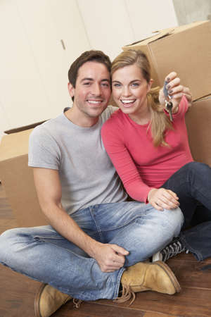 Young couple sit on the floor around boxes holding key in hand Stock Photo - 9876164
