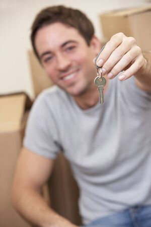 Young man sits on the floor around boxes holding a key in his hand Stock Photo - 9875588