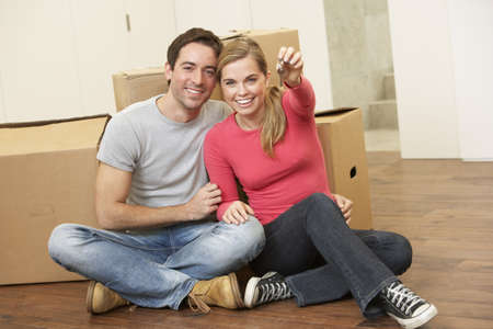 sit around: Young couple sit on the floor around boxes holding key in hand