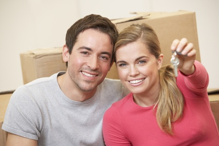 Young couple sit on the floor around boxes holding key in hand photo
