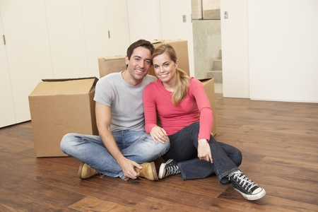 Young couple on moving day sitting with cardboard boxes Stock Photo - 9876032
