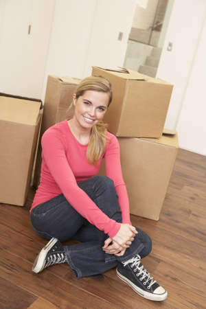 Young woman on moving day sitting on floor among cardboard boxes Stock Photo - 9876033