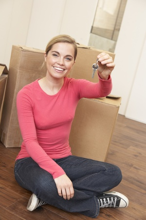 Young woman sits on the floor around boxes holding a key in her hand Stock Photo - 9875916