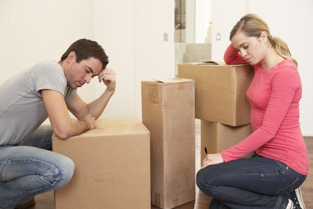 move in: Young couple looking upset among boxes Stock Photo