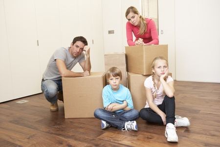 Young family looking upset among boxes photo