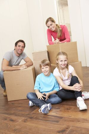 Young family on moving day looking happy among boxes Stock Photo - 9875742