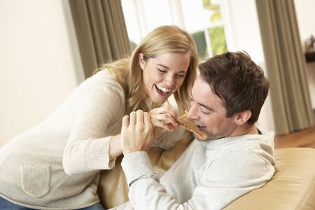 at each other: Young couple having fun laughing on sofa