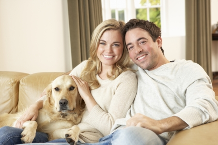 couple home: Young happy couple with dog sitting on sofa