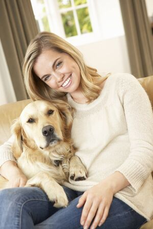 lap dog: Young woman with dog sitting on sofa Stock Photo
