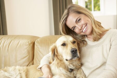 dog sitting: Young woman with dog sitting on sofa Stock Photo