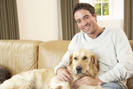 lap dog: Young man with dog sitting on sofa