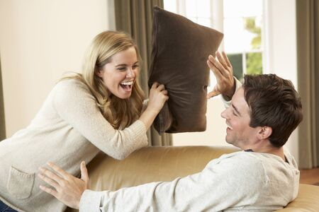 people laughing: Young couple having fun laughing on sofa
