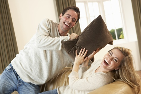 Pillow fight: Young couple having fun laughing on sofa