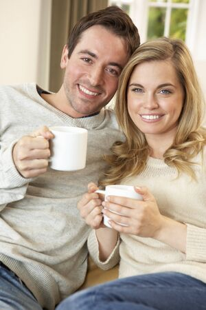 Young couple sitting and relaxing on sofa with cup in hand photo