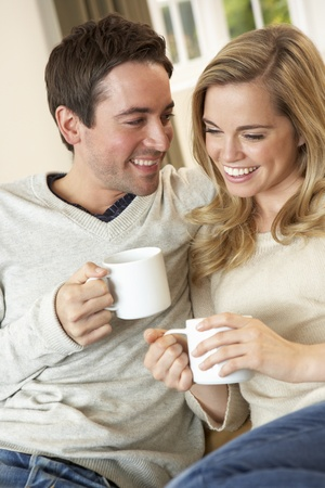 looking at each other: Young couple sitting and relaxing on sofa with cup in hand
