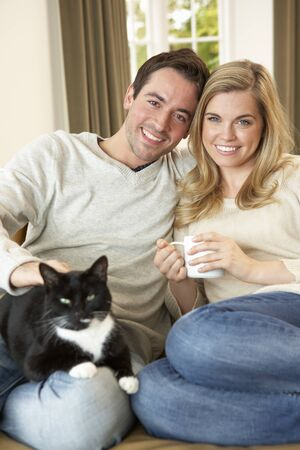 Young couple sitting with cat on sofa with cup in hand photo