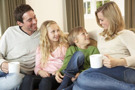 Happy young family sitting and talking on sofa photo