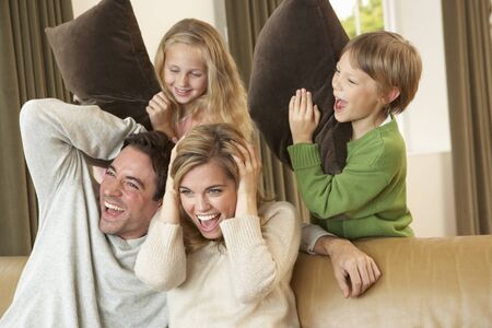 pillow fight: Happy young family having fun with pillows on sofa